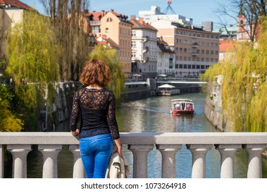 Young woman is standing on Cobblers bridge observing tourist boat on Ljubljanica river in Ljubljana old town in Slovenia.
