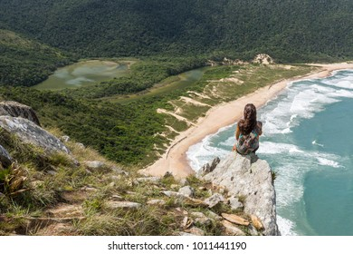 Young woman standing on the edge of a rock with a view from Pico da Coroa Hill to Lagoinha do Leste Beach, Florianopolis, Santa Catarina Island, South Brazil