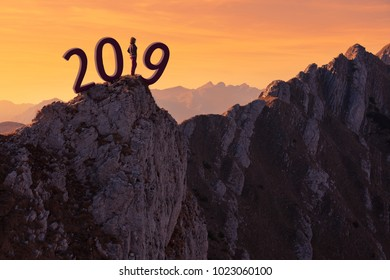 Young woman standing on edge of mountain ridge and contemplating beautiful landscape at sunset, uncertainty for upcoming 2019 new year. Future and time passing concept.