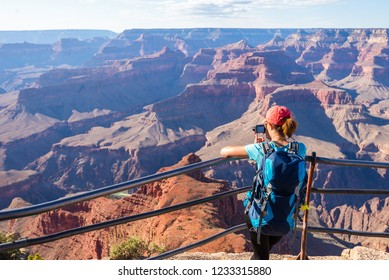 Young woman standing on the edge of Grand Canyon taking a photograph. Grand Canyon hiker woman resting. Hiking caucasian girl relaxing on  South rim of Grand Canyon, Arizona