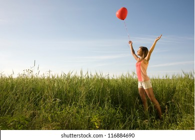 Young woman standing on the field with the red heart-shaped balloon and her arms raised