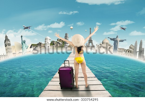 Young woman standing on the jetty while wearing swimwear and enjoy trip to the worldwide monuments