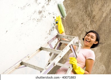 young woman standing on a ladder, painting exterior wall of her house