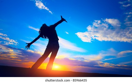 Young woman standing on meadow on sunset sky background