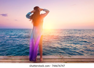 A young woman is standing on the pier and looking at the sea at sunrise