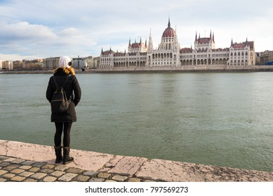 Young woman is standing on the riverbank of the Danube river and looking at Hungarian Parliament Building in BudaPest, Hungary