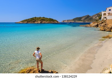 Young woman standing on rock looking at beautiful beach with turquoise sea water, Sant Elm, Mallorca island, Spain