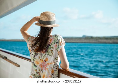 Young woman standing on the ship board and looking into the distance, rear view