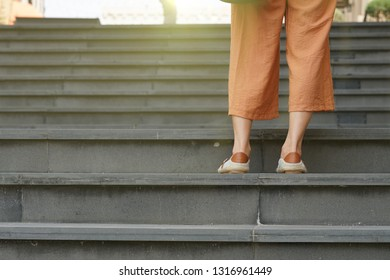 Young woman standing on the stairs with morning sun background.