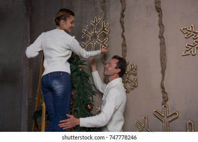 A young woman is standing on a stepladder and decorating a house for Christmas, and a man supports a ladder. A young couple decorates a house for Christmas with garlands of snowflakes