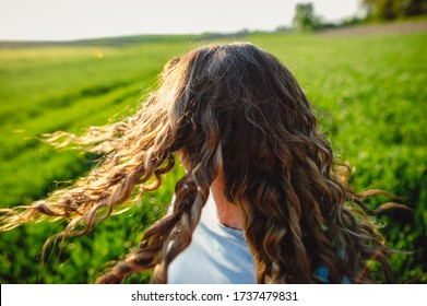 Young woman standing on street with hair blown by the wind, covering her face. Young casual girl with wavy hair. Dark-haired  woman with messy windy tousy blowsy hair, long wavy hair fly in the wind