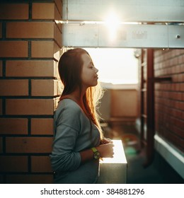 Young Woman Standing on a Street with Closed Eyes in Sunset Light. Selective Focus, Lens Flare.