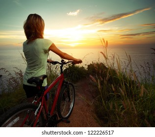 Young woman standing on top of a hill with mountain bike and enjoying the sunset sea view