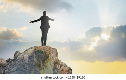 Young woman standing on the top of rock and open hands towards the sun. Success in business concept