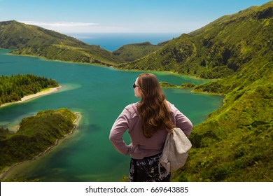 Young woman standing on top of a mountain overlooking Lagoa do Fogo in Sao Miguel, Azores, Portugal.