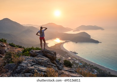 Young woman standing on the top of the rock and looking at the seashore and mountains at colorful sunset in summer. Landscape with girl, sea, mountain ridges and orange sky with sun. Oludeniz, Turkey