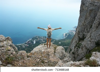 Young woman standing on top of mountain against sea at cloudy weather. Back view.