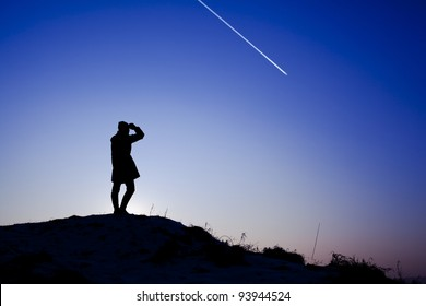 Young woman standing on the top of the hill during winter sunset. Backlit landscape.