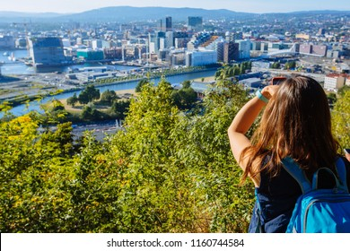 Young woman standing on the view point of Oslo and enjoying the panorama of the city. Beautiful and soft sunlight. Norway.