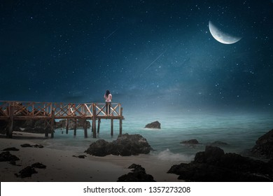 A young woman standing on a wooden bridge at the pier on the shore on a lonely half moon night