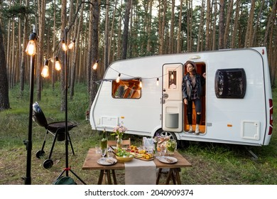 Young woman standing in open door of house on wheels among pinetrees and served table in front