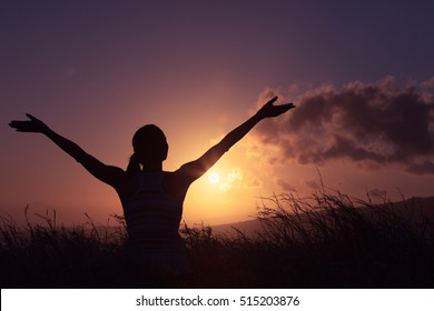 Young woman standing in a open field with her arms raised up in the air feeling happy and free.