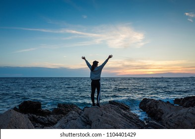 Young woman standing outdoors at sunset close Adriatic Sea in Croatia. Beautiful nature and landscape on dusk evening at the ocean in Dalmatia. Girl holding arms up in air. Calm, peaceful and happy.