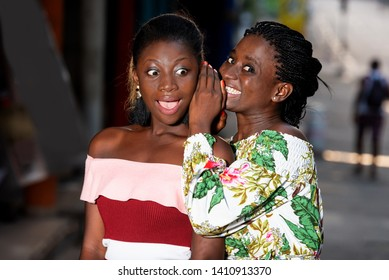 young woman standing outdoors talking to her girlfriend's ear and looking at camera smiling.