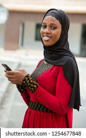 young woman standing outdoors veiled head smiling with mobile phone in hands.