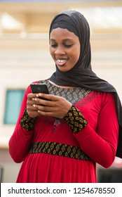 young woman standing outdoors with veiled head looking at mobile phone while smiling.