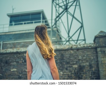 A young woman is standing outside a listening station in the fog