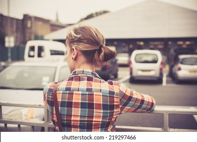 A young woman is standing outside a parking lot in the city
