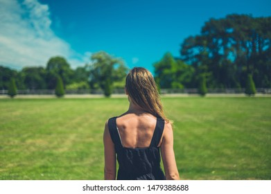 A young woman is standing in the park on a sunny summer day