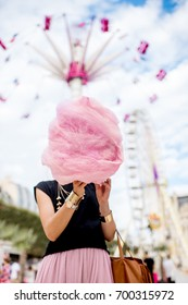 Young woman standing with pink cotton candy in front of the ferris wheel at the amusement park