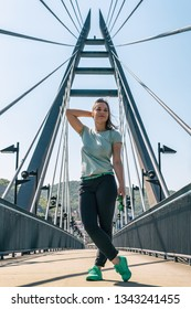 Young woman standing with raised hand on suspension bridge. Girl in green sneakers on Marian bridge in Usti nad Labem, Czech Republic.