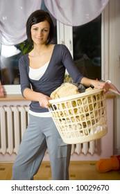 Young woman standing in room with full laundry basket. Looking at camera. Front view.