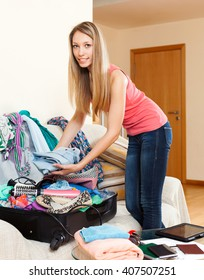 young woman standing in a room and putting things in an open suitcase