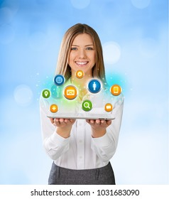 Young woman standing and smiling with many different people's faces flying from her tablet computer. Technology social media network concept