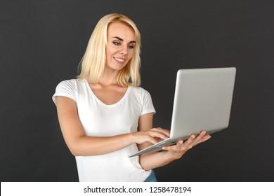 Young woman standing studio isolated on black wall browsing internet on laptop smiling joyful