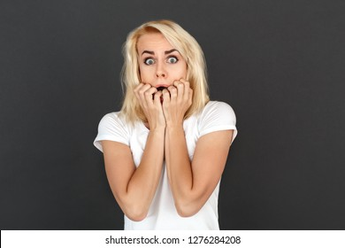 Young woman standing studio isolated on black wall looking camera biting nails scared close-up