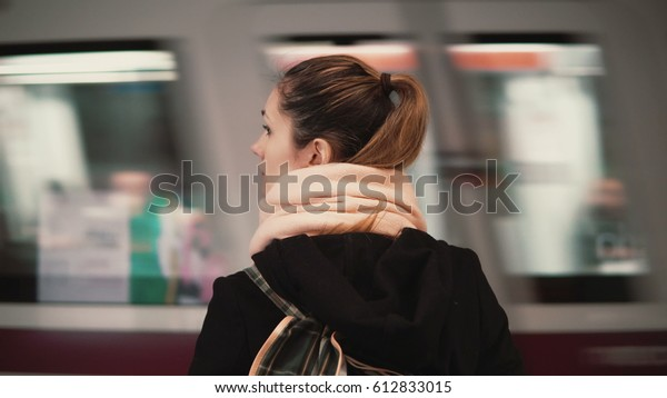 Young woman standing in the subway platform against the background of passing train. Girl waiting metro to go to job.