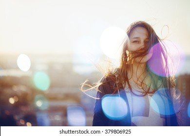 Young Woman Standing in Sunset Light, Looking at Camera. Hair Fluttering in the Wind. Selective Focus, Bokeh Lights.