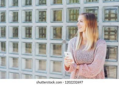 Young woman standing in town against a glass brick wall holding her obile phone looking to the side with a smile