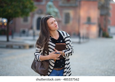 Young woman standing in the town square.She examines something with interest. In the hands of a woman has a cellphone and a notebook. In the background can be seen the beautiful buildings and monument