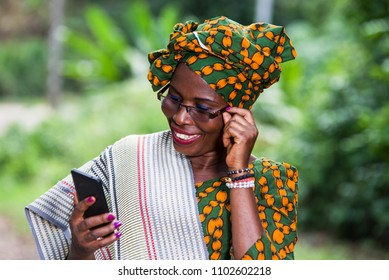 young woman standing in traditional clothes and glasses looking at mobile phone while laughing.
