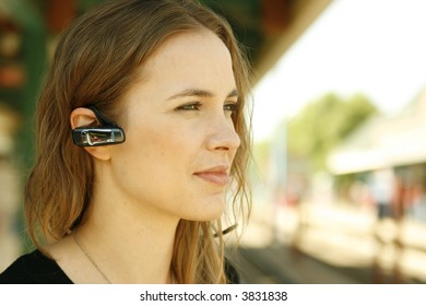 Young woman standing in train station with headset for cell phone