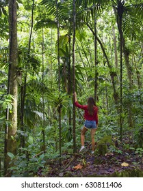 A young woman standing in the tropical jungle of Caribbean island, in exotic green forest