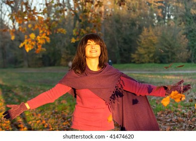 Young woman standing under falling leaves smiling under warm sunlight