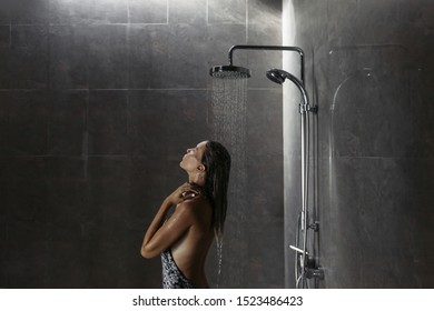 Young woman standing under shower and washing hair back to the camera over black ceramic tiles in modern luxury dark bathroom interior.