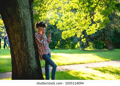 young woman is standing under a tree with a phone in hands in the summer park